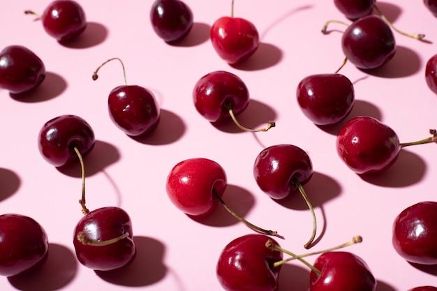 Disposizione piatta di ciliegie disordinate su uno sfondo rosa
