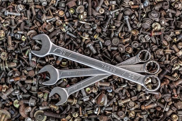 Chiavi metalliche piatte di diverse dimensioni giacciono sullo sfondo di vari ingranaggi metallici, viti e chiodi, vista dall'alto. kit attrezzi da falegname da vicino