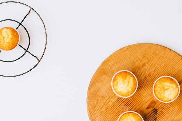 Muffin arancio casalinghi di minimalismo piano di disposizione sul bordo di legno