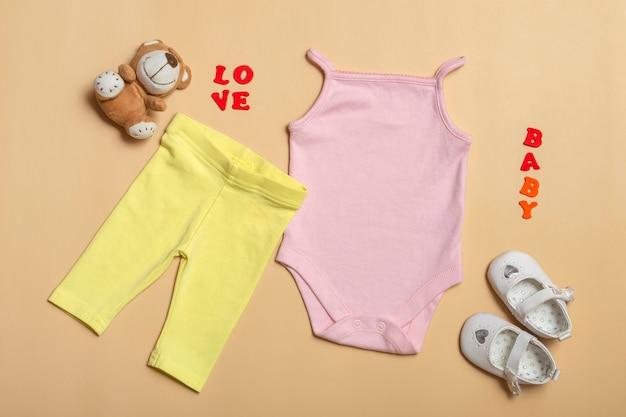 Flat lay mockup di maglietta rosa, pantaloni gialli, scarpe bianche con giocattoli su uno sfondo colorato. layout per la progettazione e il posizionamento di loghi, pubblicità.