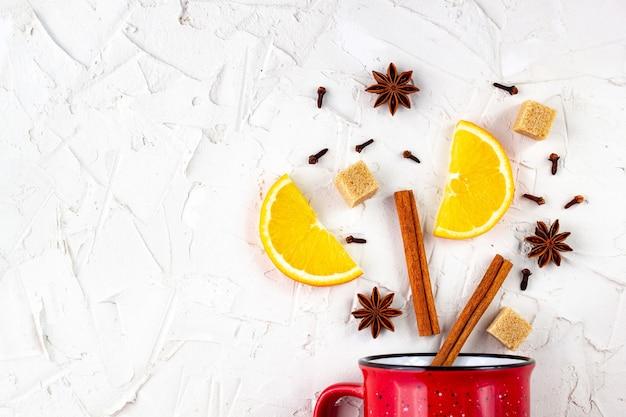 Lay piatto di vin brulè ingredienti. cannella, arancia, cardamomo, chiodi di garofano, anice stellato e tazza rossa su sfondo bianco.