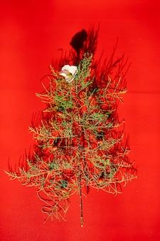 Lay piatto di foglie di ago a forma di albero di natale con fiori e bacche, albero di natale decorato su uno sfondo rosso
