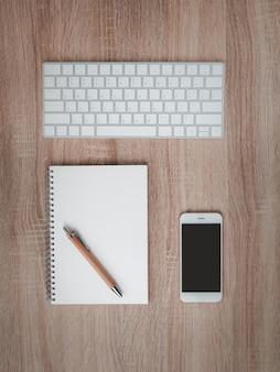 Lay piatto di notebook con penna marrone sul desktop.