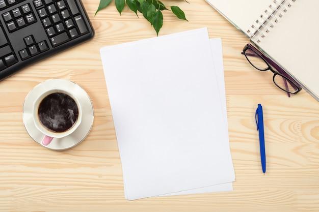 Piatto di laici tavolo da ufficio scrivania. area di lavoro con foglio di carta bianco, tastiera, forniture per ufficio, matita, foglia verde e tazza di caffè sulla tavola di legno.