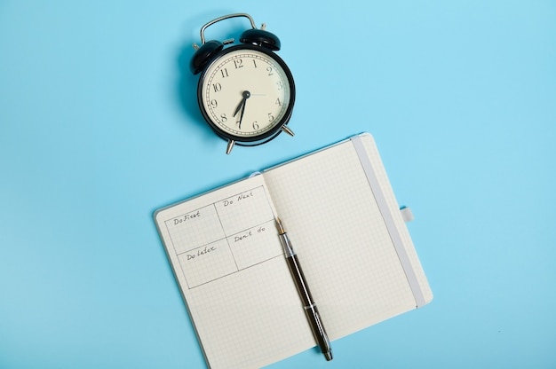 Disposizione piatta del taccuino aperto con orario del giorno per ora, penna, sveglia su sfondo colorato con spazio di copia. gestione del tempo, scadenza e concetto di corretta pianificazione e organizzazione del tempo