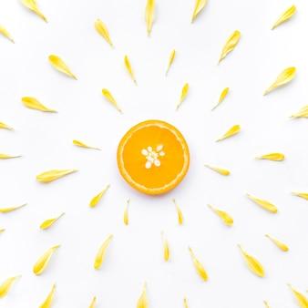 Lay piatto di fetta d'arancia con petalo di fiore su bianco