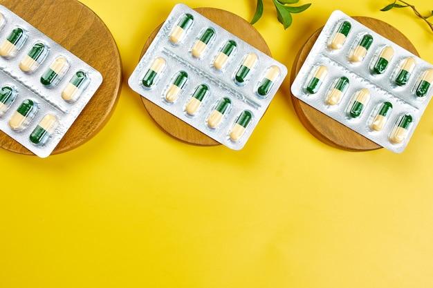 Pillole mediche organiche piatte, capsule in blister con foglia verde