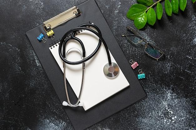 Vista sopraelevata piana del tavolo dello studio medico con il blocco note, lo stetoscopio, i vetri e la pianta verde in bianco sulla tavola rustica scura.