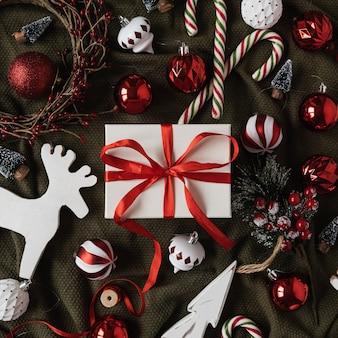 Piatto di scatola regalo di carta con farfallino e palline natalizie, bastoncini di zucchero, giocattoli sulla coperta sgualcita verde. vista dall'alto, piatto.