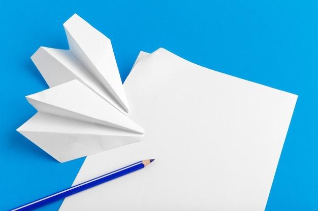 Disposizione piatta di un aeroplano di carta su sfondo di colore blu pastello