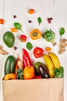 Borsa per la spesa in carta piatta con assortimento di frutta e verdura fresca, alimenti biologici e biologici su sfondo bianco, stile supermercato, alimentari, cibo vegetariano dietetico.