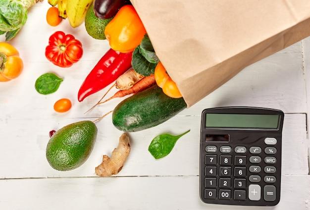 Borsa per la spesa in carta piatta con assortimento di frutta e verdura fresca e calcolatrice, cibo biologico sano e biologico su sfondo bianco, stile supermercato, drogheria, cibo vegetariano dietetico.
