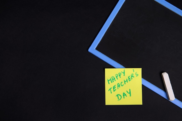 Disposizione piana di una carta per appunti gialla incollata con l'iscrizione happy teacher's day su una lavagna vuota con un gesso. sfondo nero, copia spazio