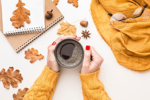 Disposizione piana della persona che tiene la tazza di caffè con le foglie di autunno
