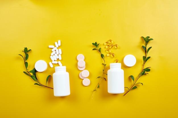 Lay piatto di pillole, olio di pesce, vitamine con foglie verdi su giallo