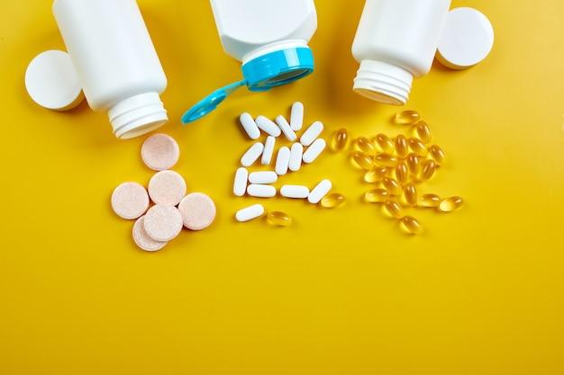 Disposizione piatta di pillole, olio di pesce, vitamine con foglie verdi sulla superficie gialla