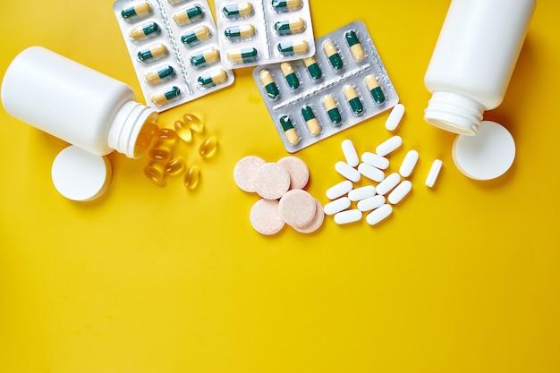 Lay piatto di pillole, olio di pesce, vitamine sulla superficie gialla