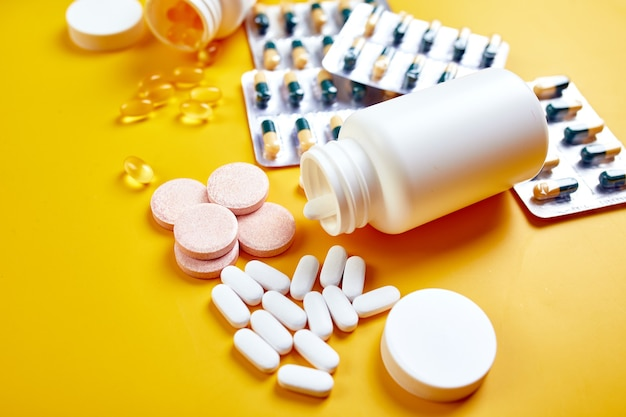 Disposizione piatta di pillole, olio di pesce, vitamine su giallo