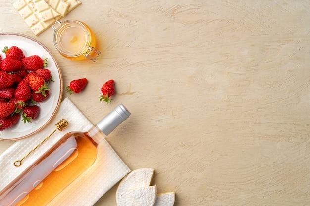 Lay piatto di bottiglia di vino rosa, fragole e formaggio sulla vista superiore della superficie grigia