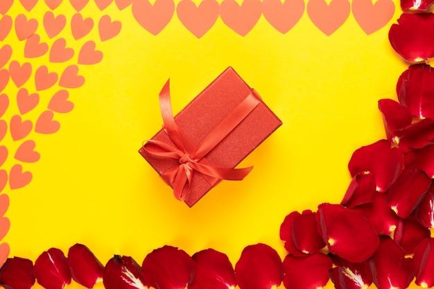 Scatola rossa piatta con fiocco vicino a petali di rosa. regalo per gli amanti