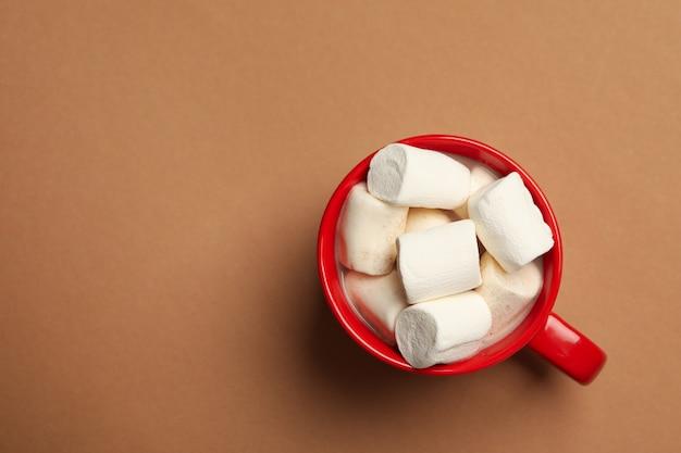 Lay piatto sulla tazza rossa con marshmallow