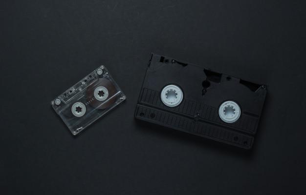 Media e intrattenimento retrò piatti. cassetta audio, vhs su sfondo nero. anni 80. vista dall'alto