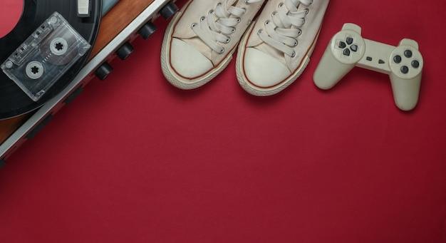 Media e intrattenimento retrò piatti. giradischi in vinile con dischi in vinile, cassette audio, gamepad, scarpe da ginnastica su sfondo rosso. copia spazio. anni 80. vista dall'alto