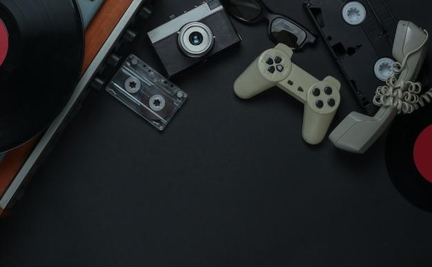 Media e intrattenimento retrò piatti. giradischi in vinile con dischi in vinile, cinepresa, videocassetta, audiocassetta, gamepad, microtelefono su uno sfondo nero. copia spazio. anni 80. vista dall'alto