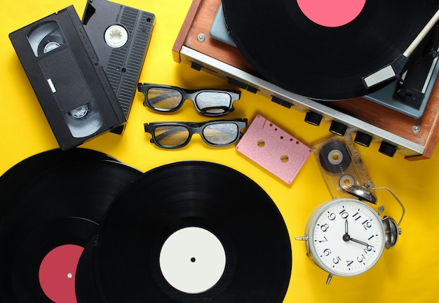 Attributi stile retrò laici piatti, media anni '80. lettore vinile, videocassette, cassette audio, dischi, occhiali 3d, sveglia vintage, vecchi libri su sfondo giallo. vista dall'alto