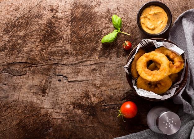 Piatto di laici ad anello patatine fritte nella ciotola con il pomodoro e lo spazio della copia