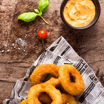 Lay piatto di patatine fritte ad anello sul giornale con senape