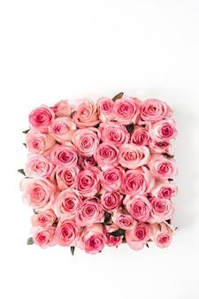 Boccioli di fiori rosa piatti laici su sfondo bianco.