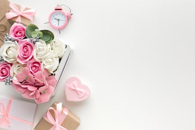 Piatto disteso di rose in scatola con orologio e regali