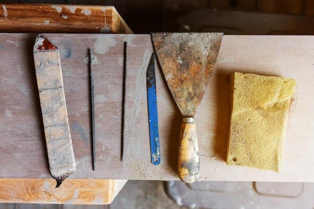 Disposizione piana di lama per sega, raschietto rustico e spugna per la fabbricazione di ceramiche per stampaggio ceramico. attrezzature per la produzione di ceramica. set di strumenti di creazione.