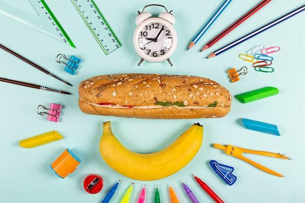 Distesi piatti di materiale scolastico su uno spazio blu minimalista.