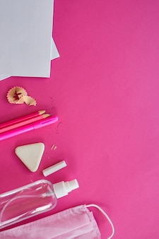 Scuole piatte dopo la pandemia di coronavirus, ritorno a scuola in una nuova realtà, materiale scolastico, maschera protettiva e antisettico su sfondo rosa, spazio per il testo