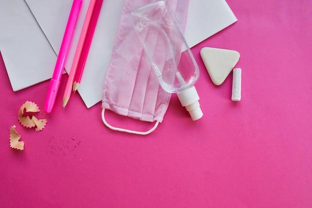 Scuola laica dopo la pandemia di coronavirus, ritorno a scuola in una nuova realtà, materiale scolastico, maschera protettiva e antisettico su sfondo rosa, spazio per il testo.