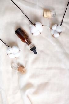 Disposizione piana della bottiglia di vetro del siero con la pipetta e bello fiore di cotone sul fondo di struttura del panno, concetto di cosmetico naturale, skinimalism, spazio della copia.