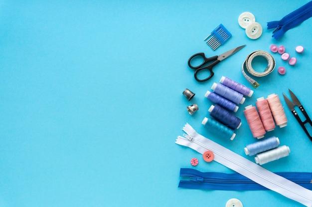 Lay piatto di accessori per cucire. fili e strumenti di sartoria sul blu