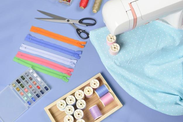 La disposizione piatta del materiale per cucire contiene i rotoli di tessuti, forbici, cerniere, perni e fili.