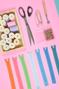 La posizione piatta del materiale per cucire contiene le forbici, il nastro di misura, la cerniera e i rotoli di filo.