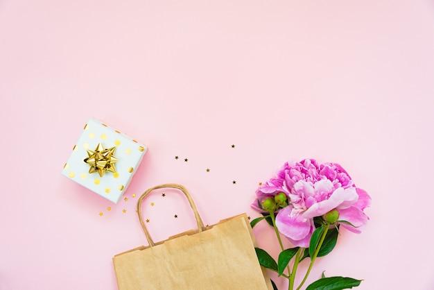 Lay piatto di shopping bag, confezione regalo e fiore di peonia su sfondo rosa. copia spazio.