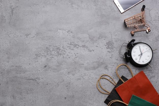 Disposizione piatta del carrello delle borse della spesa e del telefono cellulare su sfondo grigio idee sullo shopping online