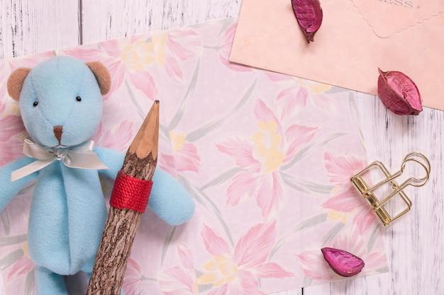 Colpo piatto laici della busta della carta della cancelleria del fiore e dei petali dell'orso sveglio che tiene matita