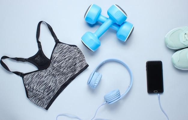 Lay piatto di uno smartphone con cuffie, manubri in plastica, reggiseno sportivo, scarpe da ginnastica su sfondo grigio