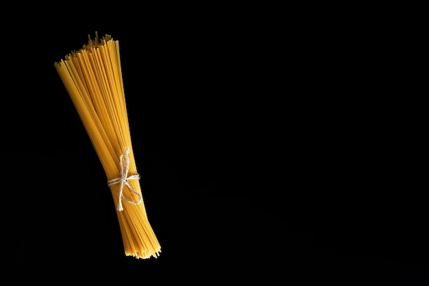 Lay piatto di spaghetti per cucinare la pasta italiana sul muro nero. vista dall'alto del concetto di cucina italiana tradizionale