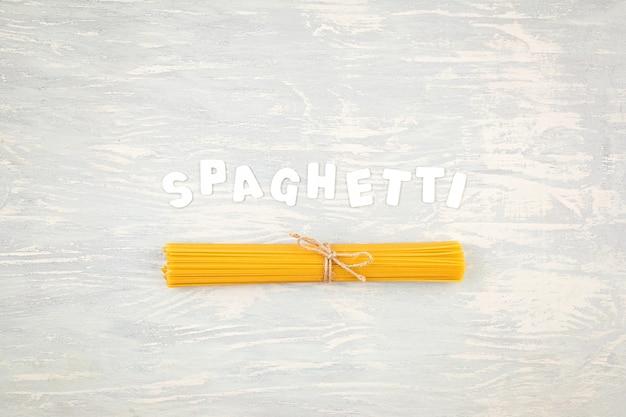 Lay piatto di spaghetti per cucinare la pasta italiana su una parete in legno chiaro. vista dall'alto del concetto di cucina italiana tradizionale