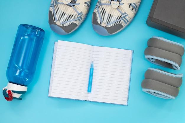 Piatto di laici attrezzature sportive e fitness su sfondo blu con copia spazio.