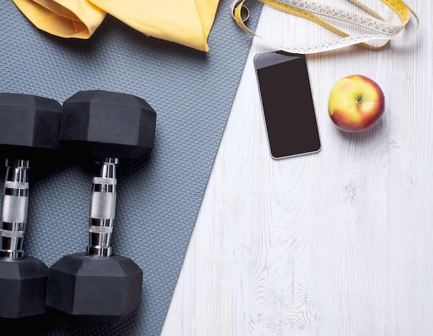 Disposizione piatta del concetto di sport: tappetino grigio, asciugamano giallo, telefono, metro, due manubri e una mela
