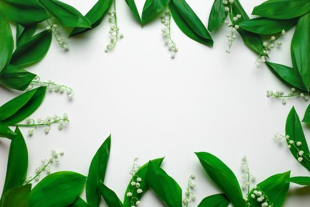 Piatto giaceva su una cornice primaverile di mughetti in fiore con foglie su uno sfondo bianco isolato...